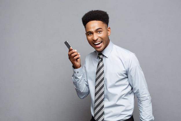Geschäftskonzept - fröhlicher professioneller afroamerikanischer geschäftsmann, der glücklich ist, auf handy mit kunden zu sprechen.