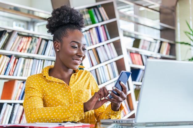 Geschäftskonzept: geschäftsfrau, die ein mobiltelefon an der schreibtischarbeit verwendet