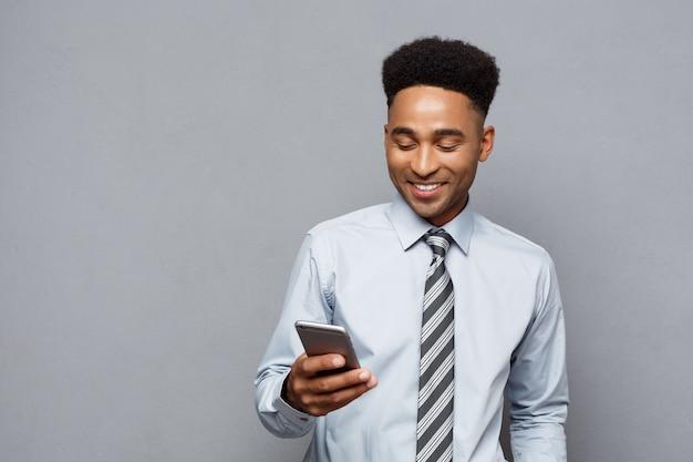 Geschäftskonzept - glücklicher hübscher professioneller afroamerikanischer geschäftsmann, der auf handy schreibt.
