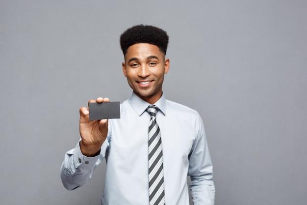 Geschäftskonzept - glücklicher hübscher professioneller afroamerikanischer geschäftsmann, der dem kunden visitenkarte zeigt.