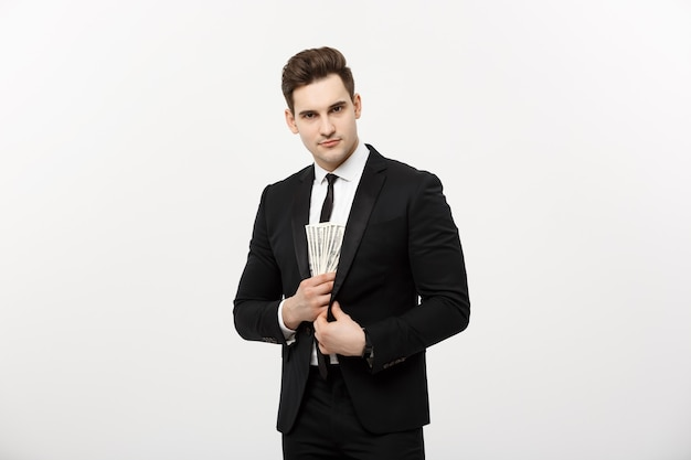 Geschäftskonzept: gut aussehender geschäftsmann im schwarzen anzug, der dollar-banknoten mit heimlichem ausdruck gegen weißen hintergrund nimmt.