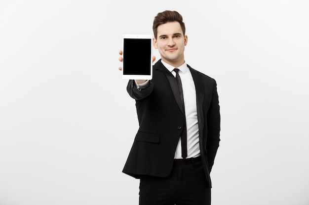 Geschäftskonzept: lächelnder gutaussehender geschäftsmann, der website oder präsentation auf tablet darstellt.