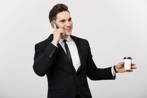 Geschäftskonzept: nahaufnahme überzeugter junger gutaussehender geschäftsmann, der auf handy spricht und kaffee über weißem lokalisiertem hintergrund trinkt.