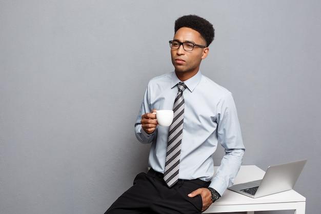 Geschäftskonzept - porträt des afroamerikanergeschäftsmannes, der kaffee sitzt, der an einem schreibtisch unter verwendung eines laptops sitzt.
