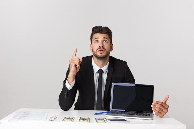 Geschäftskonzept: porträt des gutaussehenden geschäftsmannes gekleidet im anzug, der im büro zeigt finger auf kopierraum und laptop lokalisiert über graue wand