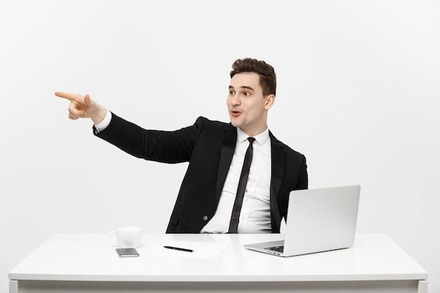 Geschäftskonzept porträt eines gutaussehenden geschäftsmannes im anzug, der im büro sitzt und mit dem finger zeigt ...