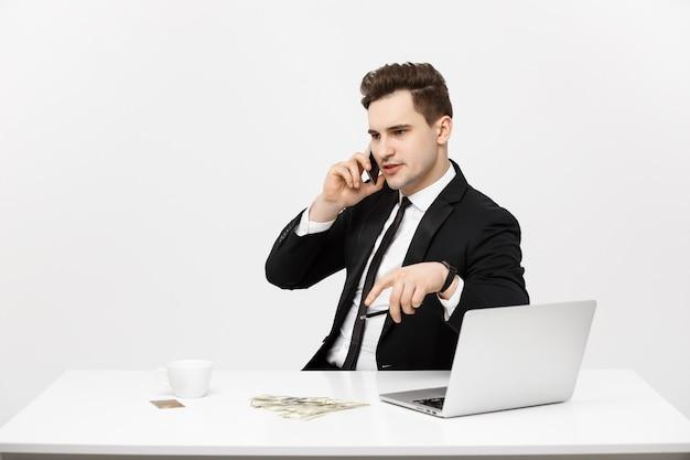 Geschäftskonzept porträt junger erfolgreicher geschäftsmann, der in hellem büro mit laptop arbeitet und spricht...