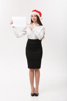 Geschäftskonzept - schöne junge kaukasische geschäftsfrau mit weihnachtsmütze, die auf leeres papier zeigt, das für werbung verwendet.