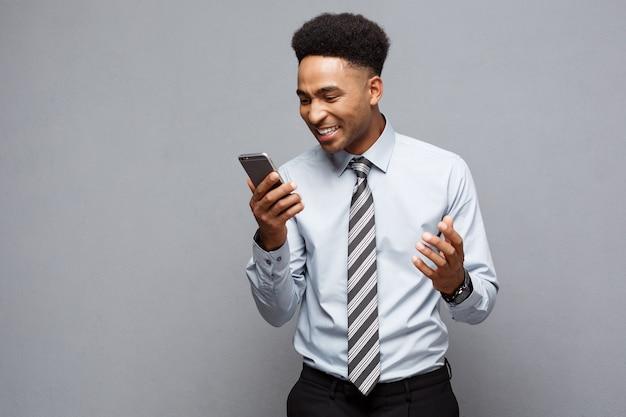 Geschäftskonzept - stressiger afroamerikanischer geschäftsmann, der auf dem mobiltelefon schreit und schreit.