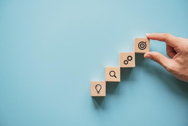 Geschäftskonzept-wachstumserfolgsprozeß, frauenhand, die hölzernen block mit ikonengeschäftsstrategie und aktionsplan, kopienraum vereinbart.