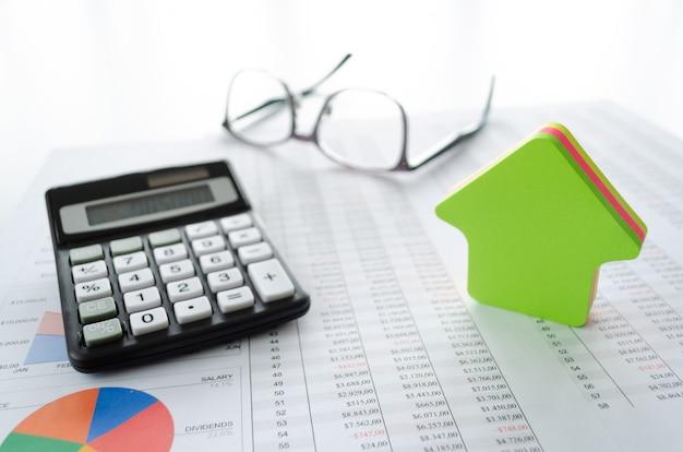 Geschäftskonzept zum kaufen oder sparen für ein haus mit, taschenrechner, brille, hausform und dokumenten