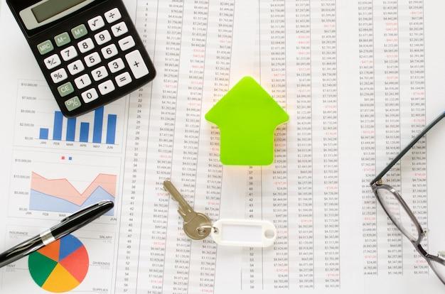 Geschäftskonzept zum kaufen oder sparen für ein haus mit, taschenrechner, brille, stift, schlüssel, hausform und dokumenten. draufsicht.