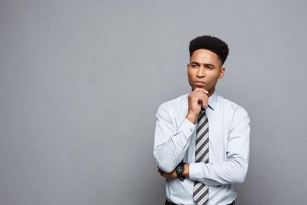 Geschäftskonzept - zuversichtlicher professioneller afroamerikanischer geschäftsmann in der denkhaltung über graue wand.