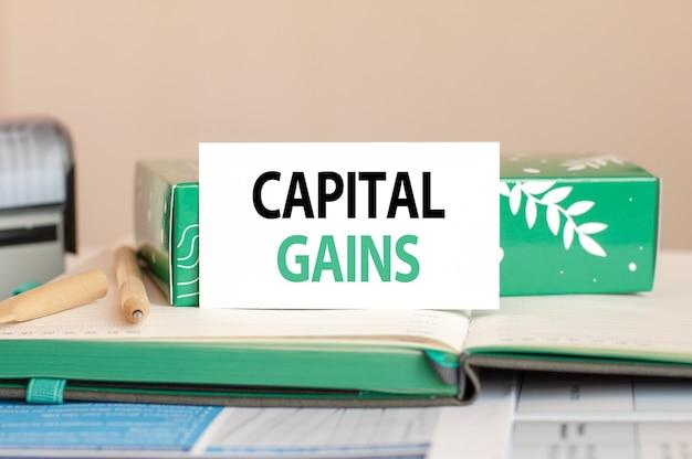 Geschäftskonzeptblatt des weißen papiers für notizen mit text capital gains