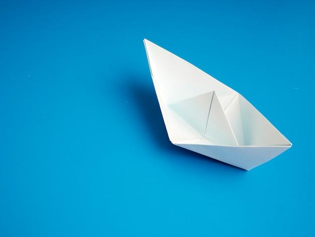 Geschäftskonzeptorigami weißes bootspapier minimal auf blauem hintergrund