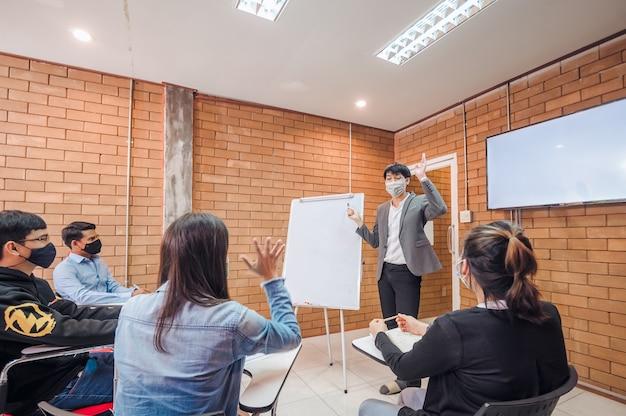 Geschäftskooperation: junge asiatische männliche trainer oder sprecher machen flipchart-präsentation für verschiedene geschäftsleute bei treffen im büro männlicher tutor oder trainer stellt verschiedenen kollegen das projekt vor.