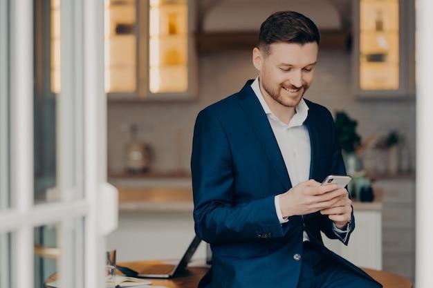 Geschäftslebensstil. froher, gutaussehender mann mit stoppeln verwendet handy für sms-online-checks newsfeed trägt elegante kleidungsposen gegen verschwommenen coworking space. fokussierter verkäufer mit gadget