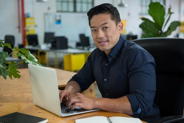 Geschäftsleiter, der am schreibtisch mit laptop sitzt