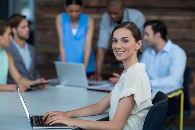 Geschäftsleiter, der auf tisch sitzt und laptop im büro verwendet