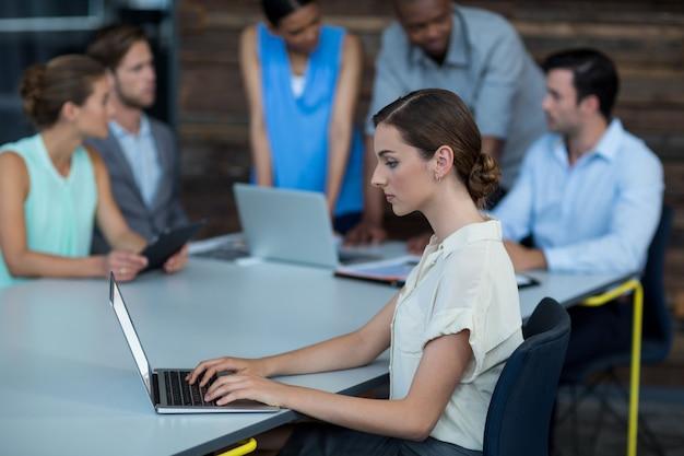 Geschäftsleiter, der auf tisch sitzt und laptop verwendet