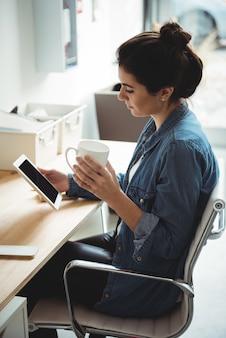Geschäftsleiter, der digitales tablett beim kaffeetassen verwendet