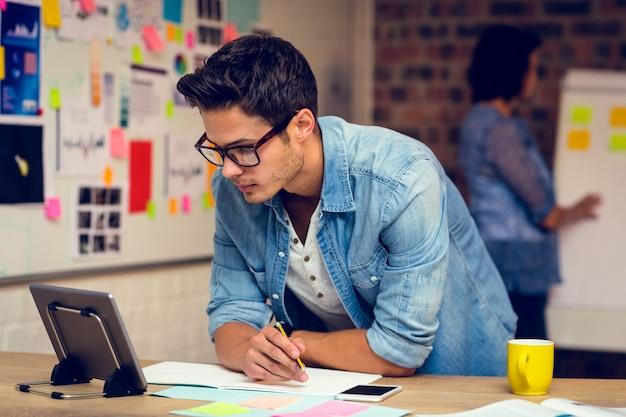 Geschäftsleiter, der digitales tablett betrachtet und notizen im tagebuch macht