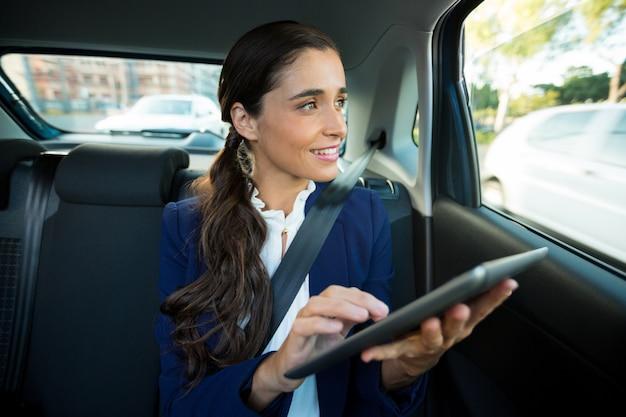 Geschäftsleiter, der digitales tablett im auto verwendet