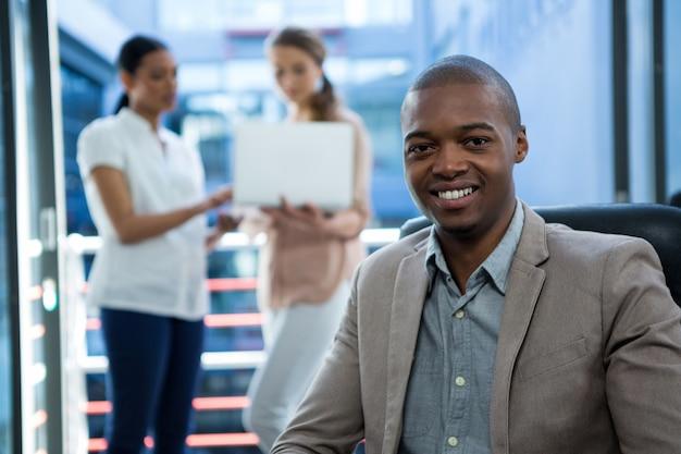 Geschäftsleiter, der im büro lächelt