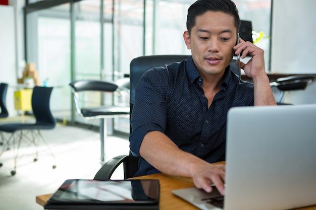 Geschäftsleiter, der laptop benutzt und auf handy spricht