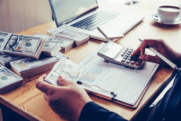Geschäftsleute arbeiten an dollars, berechnen gewinne und verdienen ergebnisse,