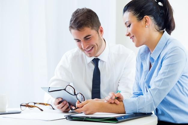 Geschäftsleute arbeiten im büro mit digitaler tablette.