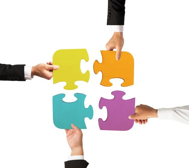 Geschäftsleute arbeiten zusammen, um ein farbiges puzzle zu bauen
