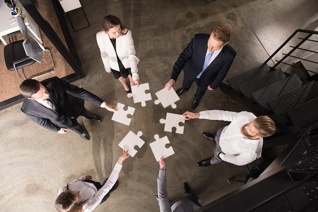 Geschäftsleute arbeiten zusammen, um ein großes puzzle zu bauen. konzept von teamwork, partnerschaft, integration und startup.