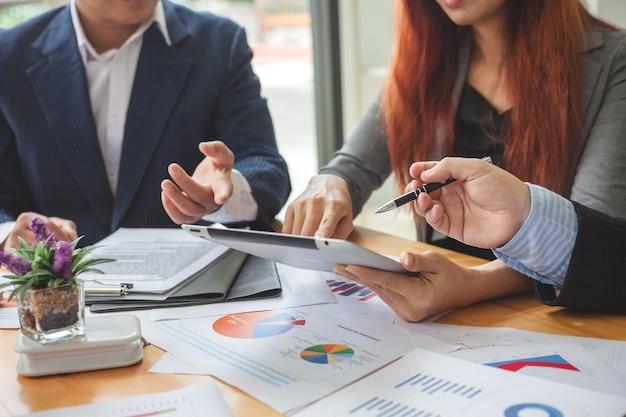 Geschäftsleute beim arbeiten mit finanzberichten und einer tablette.