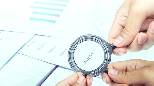 Geschäftsleute benutzen ein vergrößerungsglas, um die daten und die statistiken des unternehmens zu analysieren