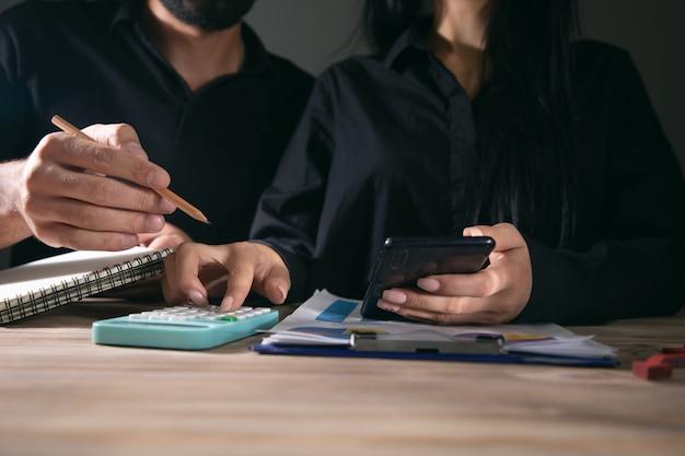 Geschäftsleute benutzen handy und taschenrechner auf dem schreibtisch