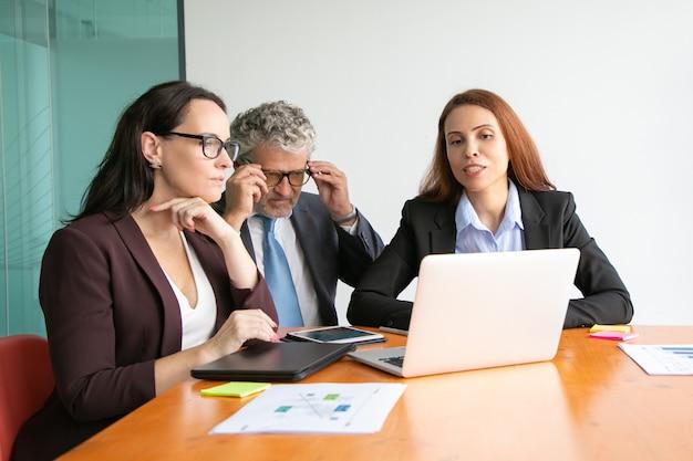 Geschäftsleute beobachten projektpräsentation auf laptop, sitzen am besprechungstisch mit papierberichten und diagrammen.
