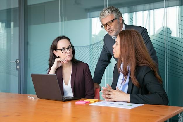 Geschäftsleute beobachten und diskutieren präsentation auf dem pc, während sie zusammen am besprechungstisch sitzen und stehen