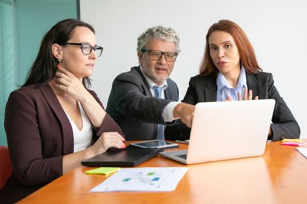 Geschäftsleute beobachten und diskutieren präsentation auf laptop, schauen und zeigen auf anzeige