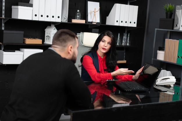 Geschäftsleute betrachten leeren laptopschirm bei der sitzung im stilvollen büro