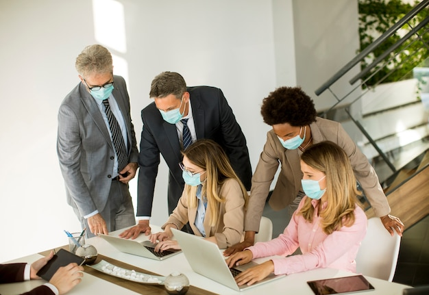 Geschäftsleute der gruppe treffen sich und arbeiten im büro und tragen als schutz masken
