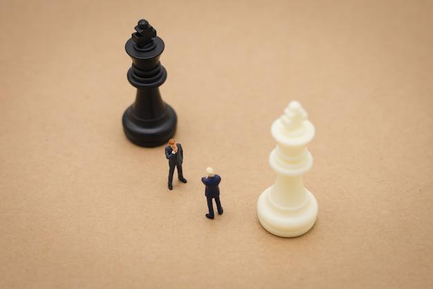 Geschäftsleute der miniatur 2 leute, die mit der rückseite stehen, die im geschäft verhandelt.