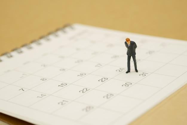 Geschäftsleute der miniaturleute, die auf weißem kalender stehen