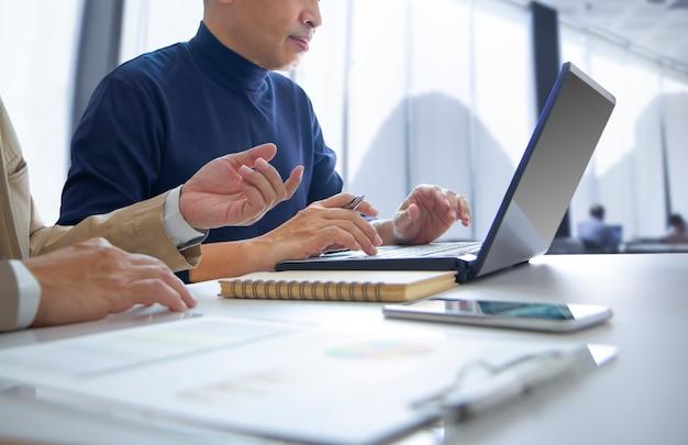 Geschäftsleute, die abschlüsse mit laptop überprüfen