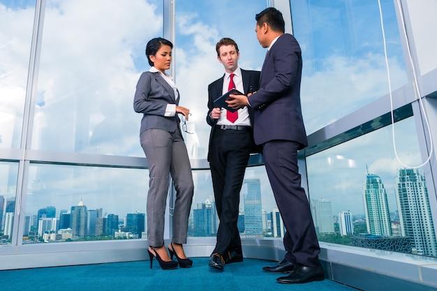 Geschäftsleute, die am bürowindo arbeiten