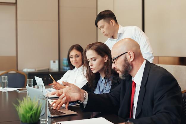 Geschäftsleute, die am konferenztische zusammenarbeiten