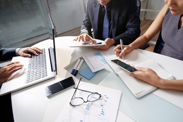 Geschäftsleute, die am schreibtisch arbeitet an projekt sitzen