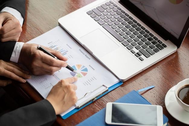 Geschäftsleute, die am schreibtisch brainstorming sind, sie analysieren finanzberichte