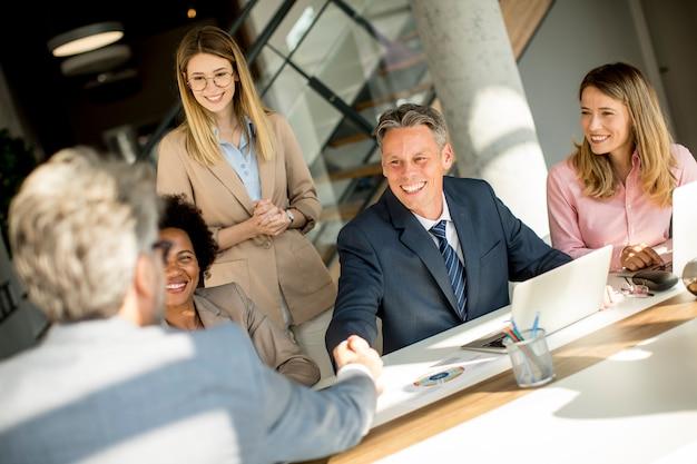 Geschäftsleute, die am schreibtisch im büro händeschütteln