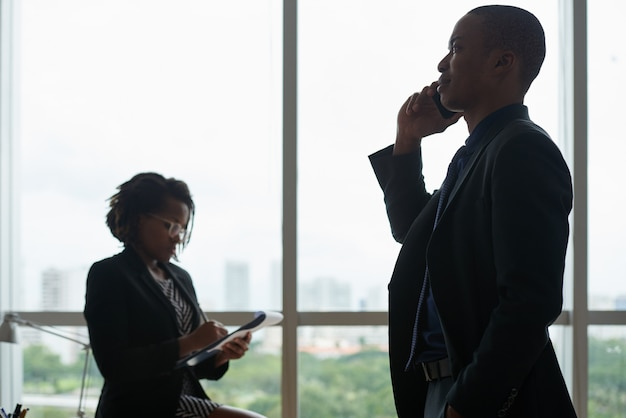 Geschäftsleute, die am telefon sprechen und in notizbuch gegen bürofenster schreiben